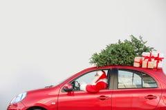 Santa Claus authentique conduisant la voiture rouge avec des boîte-cadeau images stock