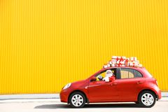 Santa Claus authentique conduisant la voiture rouge avec des boîte-cadeau photographie stock