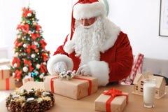 Santa Claus authentique enveloppant le cadeau à la table photographie stock
