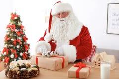 Santa Claus authentique enveloppant le cadeau à la table photographie stock libre de droits
