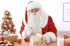 Santa Claus authentique faisant le jouet à la table photos stock