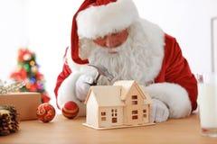 Santa Claus authentique faisant le jouet à la table photos libres de droits
