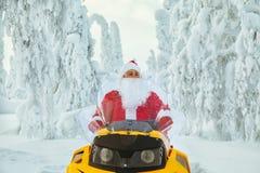 Santa Claus authentique monte un motoneige par l'hiver image stock