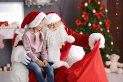 Santa Claus authentique montrant son sac avec des cadeaux à la fille à l'intérieur images libres de droits