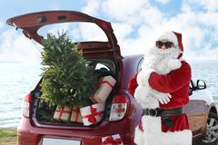 Santa Claus authentique près de voiture rouge avec le cadeau et d'arbre de Noël sur la plage images stock