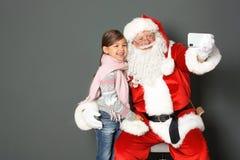 Santa Claus authentique prenant le selfie avec la fille sur le fond gris image libre de droits