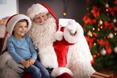 Santa Claus authentique prenant le selfie avec le petit garçon image stock