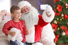 Santa Claus authentique prenant le selfie avec le petit garçon photo libre de droits