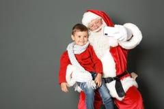 Santa Claus authentique prenant le selfie avec le petit garçon sur le fond gris photographie stock libre de droits