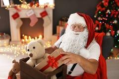 Santa Claus authentique tenant la caisse en bois avec des cadeaux photo libre de droits