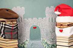 Santa Claus and author of story. Unusual Santa Claus and author of story from books before blackboard with drawing chalk of castle Stock Image