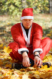Santa Claus in autumnal park. Man in santa claus suit sitting on fallen leaves in autumnal park Stock Images