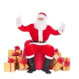 Santa Claus avec beaucoup de boîte-cadeau autour, des pouces lèvent le gesturin de main Image libre de droits