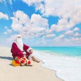 Santa Claus avec beaucoup de cadeaux d'or de Noël détendant sur le tropica Photographie stock libre de droits