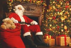 Santa Claus avec des cadeaux autour d'arbre de Noël Photographie stock libre de droits