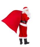 Santa Claus avec des cadeaux de Noël mettent en sac d'isolement sur le backgroun blanc Photos stock