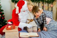 Santa Claus avec deux enfants lisant un livre Photo stock