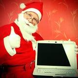 Santa Claus avec l'ordinateur portable Image stock