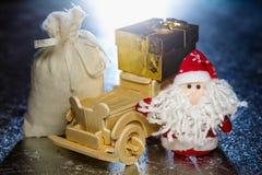 Santa Claus avec la voiture, le boîte-cadeau et le sac en bois Photographie stock