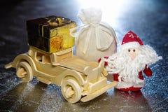 Santa Claus avec la voiture, le boîte-cadeau et le sac en bois Image stock