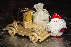 Santa Claus avec la voiture, le boîte-cadeau et le sac en bois Photo stock