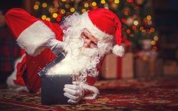 Santa Claus avec le cadeau rougeoyant magique de cadeau de Noël Photos stock