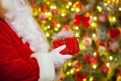 Santa Claus avec le giftbox sur le fond du sapin de scintillement Photos stock