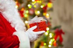 Santa Claus avec le giftbox sur le fond du sapin de scintillement Images stock