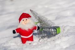 Santa Claus bär ett silvrigt träd i en vagn för ferierna kortjul som greeting Glad jul och lyckligt nytt år Arkivbilder