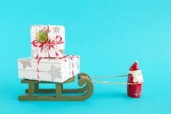 Santa Claus bär träsläden med två gåvaaskar som slås in av vit-grå färger papper, dekorerat av granfilial på blå bakgrund fotografering för bildbyråer