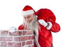 Santa Claus bärande påse mycket av gåvor som ser i lampglas Arkivbilder