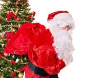 Santa Claus bärande säck vid julträdet. Arkivfoton