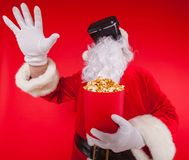 Santa Claus bärande virtuell verklighetskyddsglasögon och en röd hink med popcorn, på en röd bakgrund Jul Arkivfoton