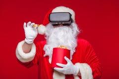 Santa Claus bärande virtuell verklighetskyddsglasögon och en röd hink med popcorn, på en röd bakgrund Jul Arkivfoto