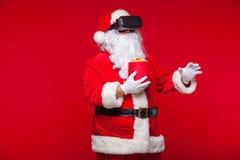 Santa Claus bärande virtuell verklighetskyddsglasögon och en röd hink med popcorn, på en röd bakgrund Jul Arkivbild