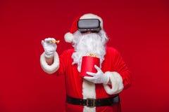 Santa Claus bärande virtuell verklighetskyddsglasögon och en röd hink med popcorn, på en röd bakgrund Jul Royaltyfria Bilder