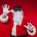 Santa Claus bärande virtuell verklighetskyddsglasögon, på en röd bakgrund Jul Fotografering för Bildbyråer