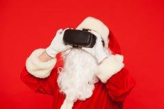 Santa Claus bärande virtuell verklighetskyddsglasögon, på en röd bakgrund Jul Royaltyfri Bild