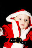 Santa claus baby. A portrait of a baby dressed up in christmas outfit on black background Royalty Free Stock Image