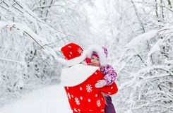 Santa claus and with baby girl in winter forest. royalty free stock photo