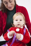 Santa claus baby with mother looking at camera Stock Image