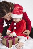 Santa claus baby with mother opening golden gift Royalty Free Stock Photos