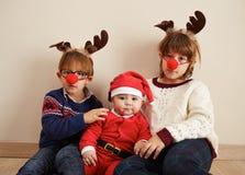 Santa Claus baby and siblings Royalty Free Stock Photography