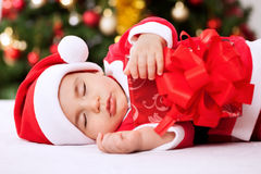 Santa claus baby sleeping and holding present Stock Images