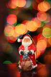 Santa Claus on a background of lights. Toy Santa Claus on a Christmas background of colorful lights, fabulous bokeh royalty free stock images