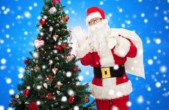 Santa claus with bag and christmas tree Stock Photo