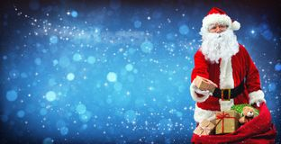 Santa Claus with a bag full of presents. On blue snowy background with magical stars stock image