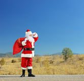 Santa claus with bag full of presents standing on an open road a. Full length portrait of a Santa claus with bag full of presents standing on an open road and Royalty Free Stock Photos
