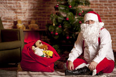 Santa Claus with a bag of gifts. On the background of the Christmas tree Royalty Free Stock Photo