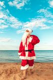 Santa Claus with a bag of gifts on the beach. The symbol of Chri. Stmas Stock Photography